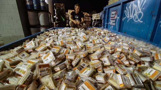 Baldwin kneeling in front of a dumpster full of Hummus that was still good, yet thrown out.